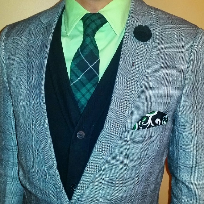 A mint shirt and subtly plaid grey blazer complement the tie and lapel pin in the green version of the Hamilton Box.