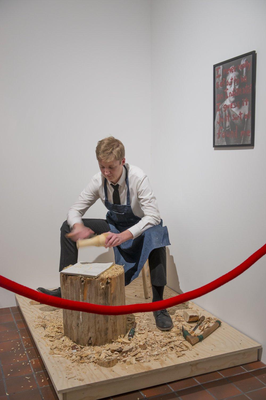 White Carver,  velvet rope, wood stump, wooden platform, white male performer, 2012-present.