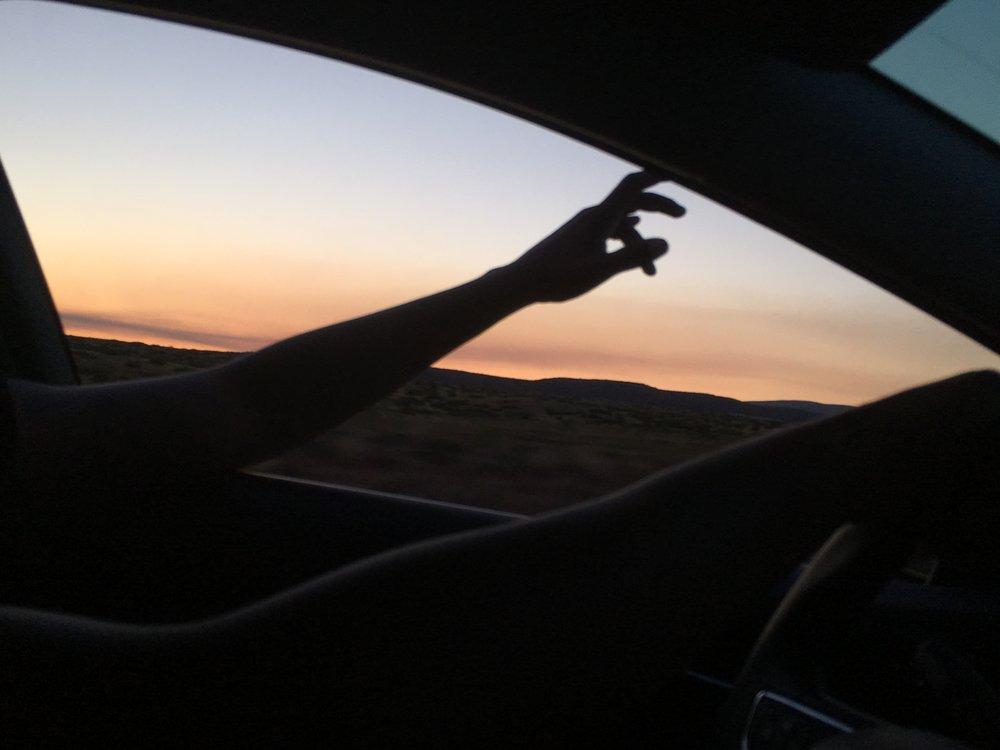 Driving through the desert at sunset.