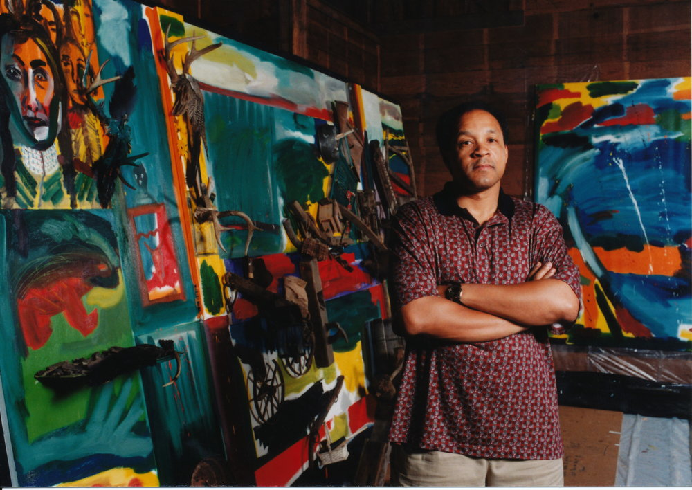 Frederick J. Brown standing in front of   Spirits of Spirit   Lake     1997    Mixed media mural   7 x 15 ft.     Collection of the SAMI Bedell Center for the Performing Arts, Spirit Lake, Iowa