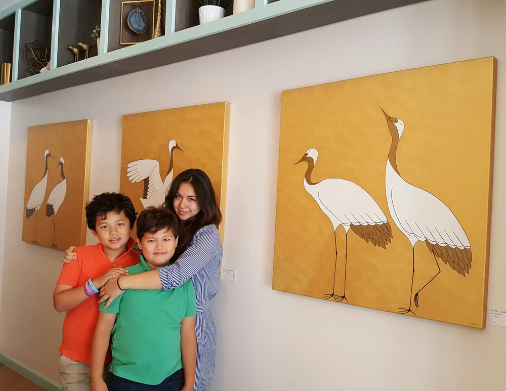 Elaine's children Hayden, Harrison and Julia at Buttercream Bakeshop (a woman run business that Elaine has invested in) standing in front of Julia's artwork.