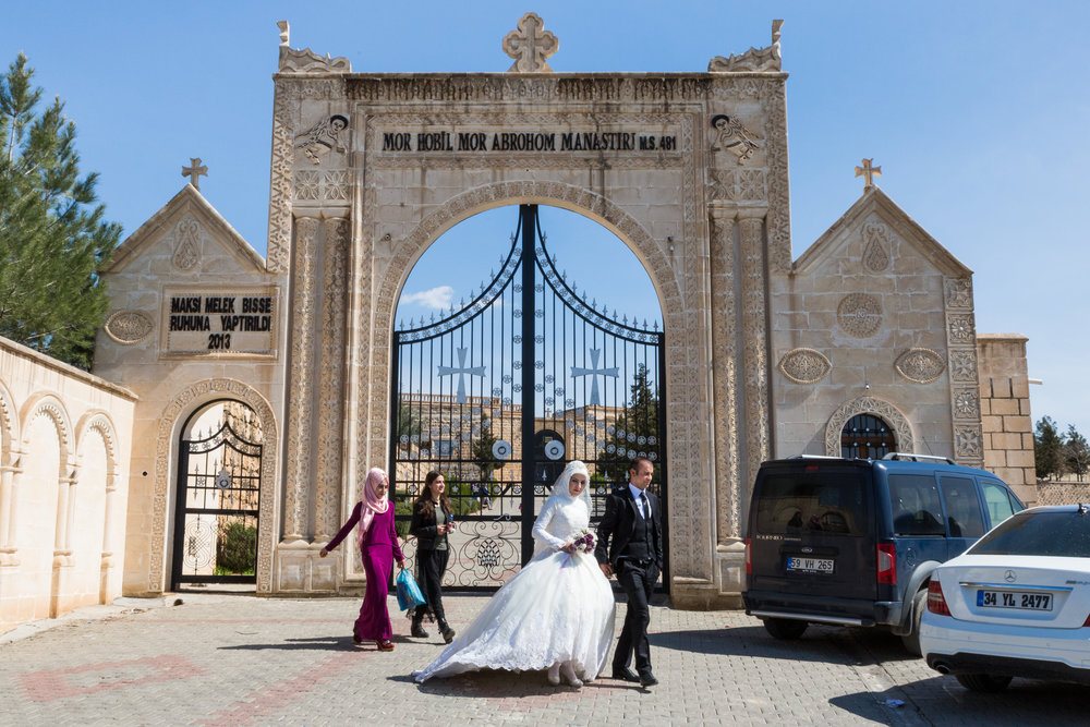 A muslim newlywed couple leaves the courtyard of Mor Hobil Monastery.