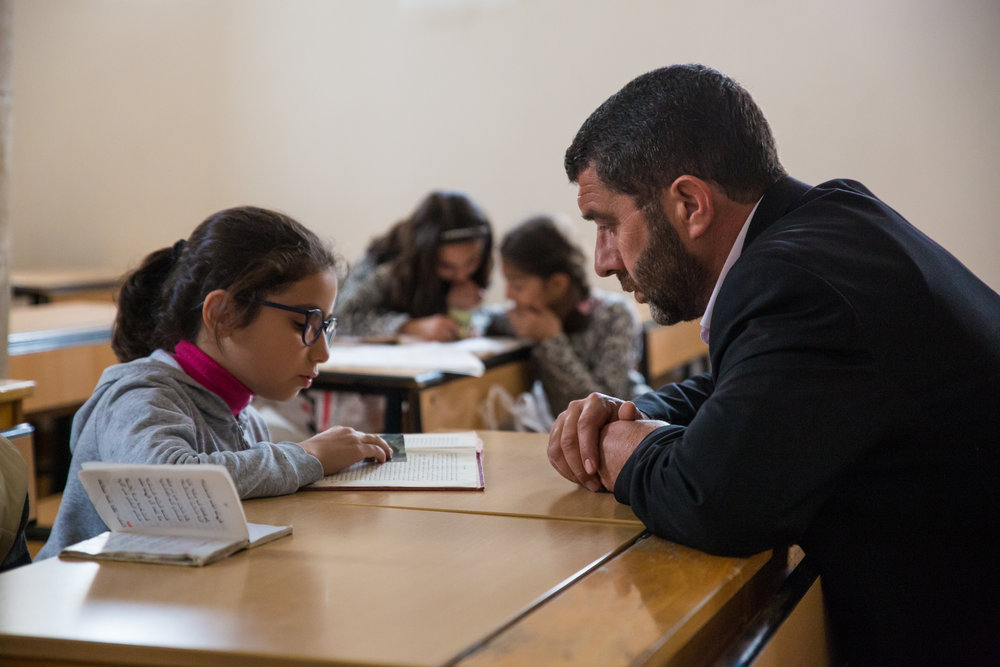 Deacon Ayhan Gürkan guides students at Mor Barsaumo in their study of the Turoyo language.
