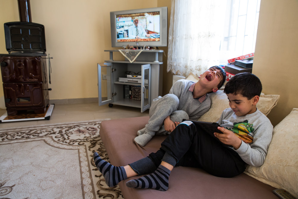 The youngest Demir plays games on an iPad with his friend.