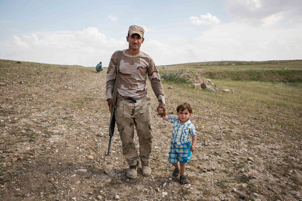 A member of the 9th Armored Division walks with a child across Iraqi lines.
