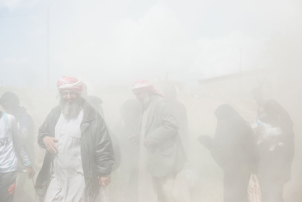 A fine dust from passing vehicles covers civilians fleeing from Islamic State territory.