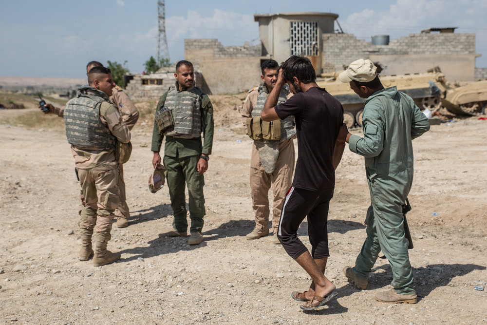 A tank crew member pulls a man out of the stream of refugees on suspicion of being an Islamic State militant