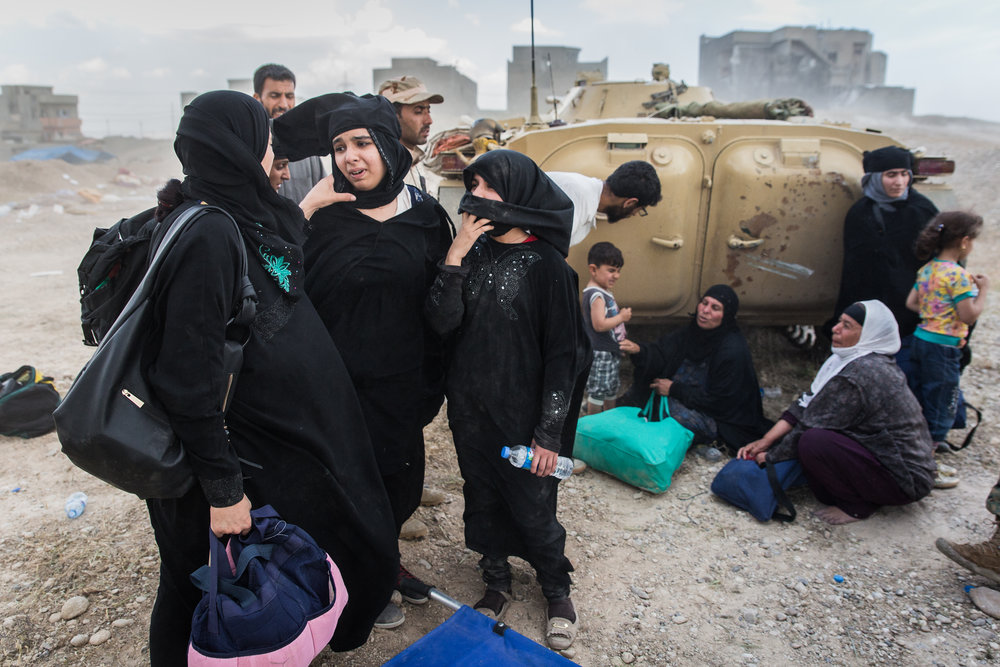 Displaced women comfort each other after arriving at Iraqi lines