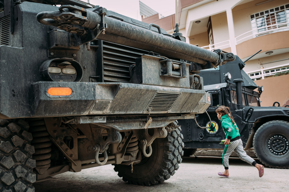"""A girl runs between an Iraqi humvee and an American Special Forces MRAP with """"Liberty Promise"""" written on the front rail."""