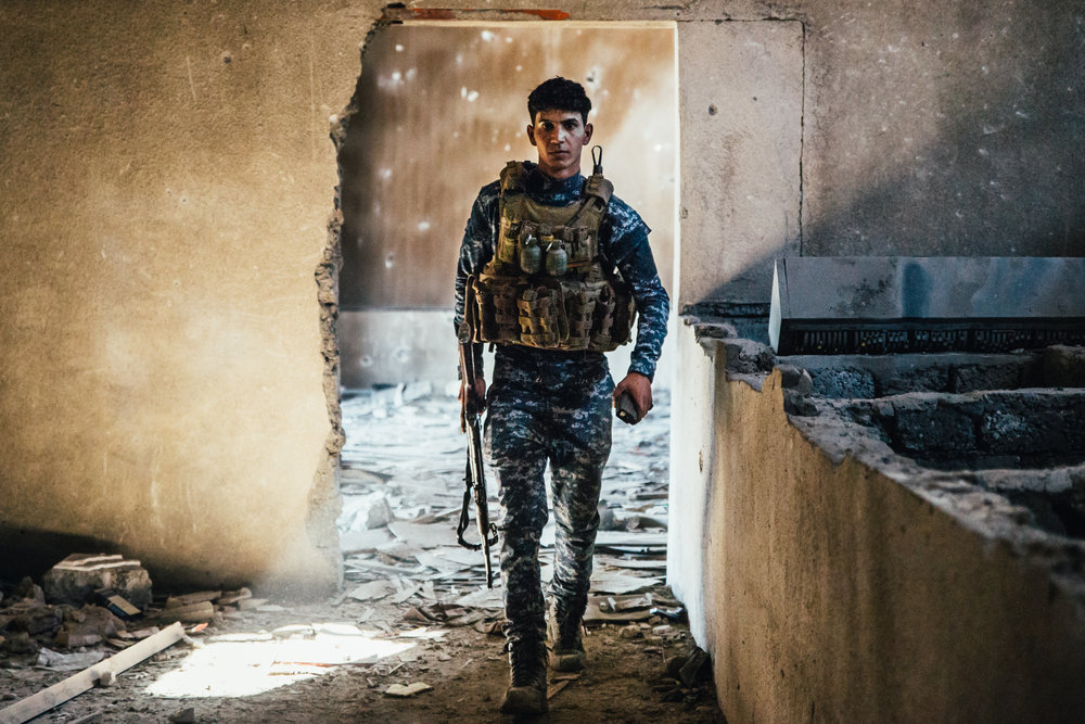 A Federal Policeman walks between fighting positions in a movie theater in west Mosul