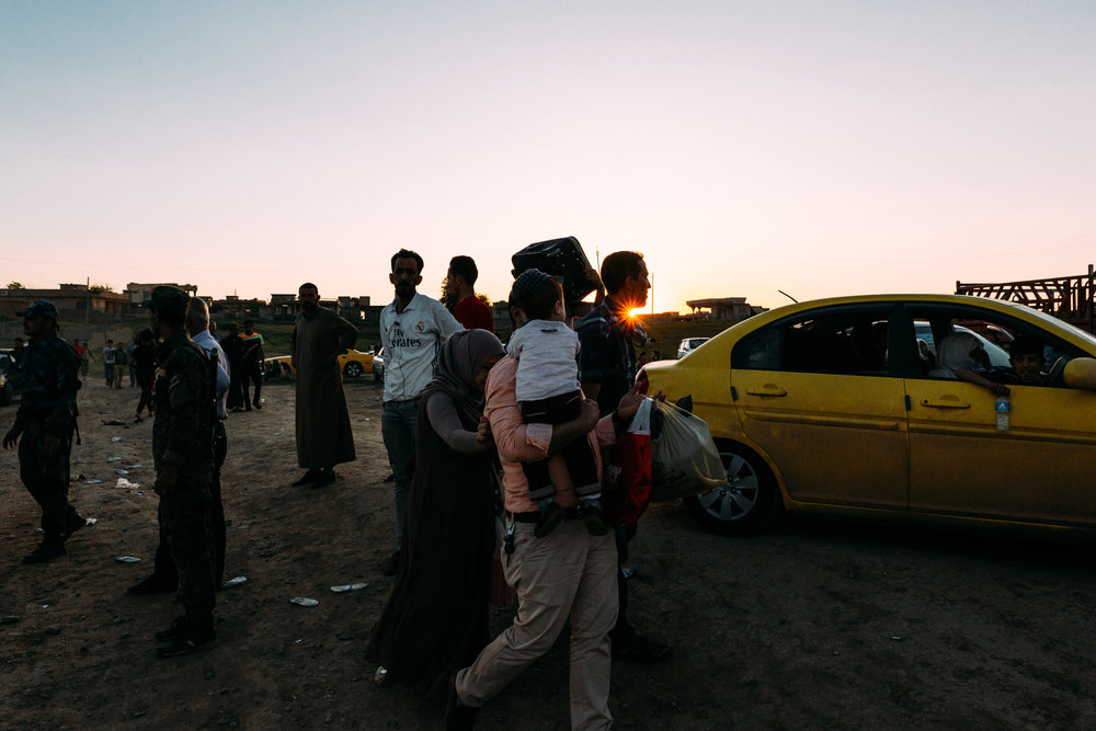 IDPs wait to pass a traffic jam over the Tigris River.