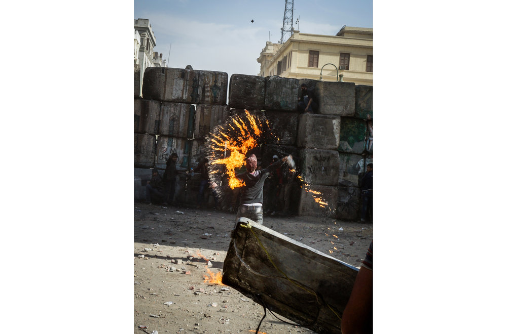 A protester throws a broken Molotov cocktail over a block wall at police guarding the Interior Ministry.