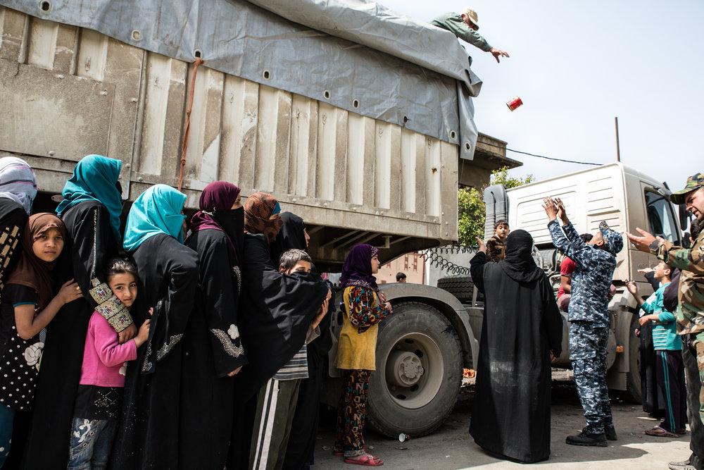 Civilians queue for food distribution in west Mosul