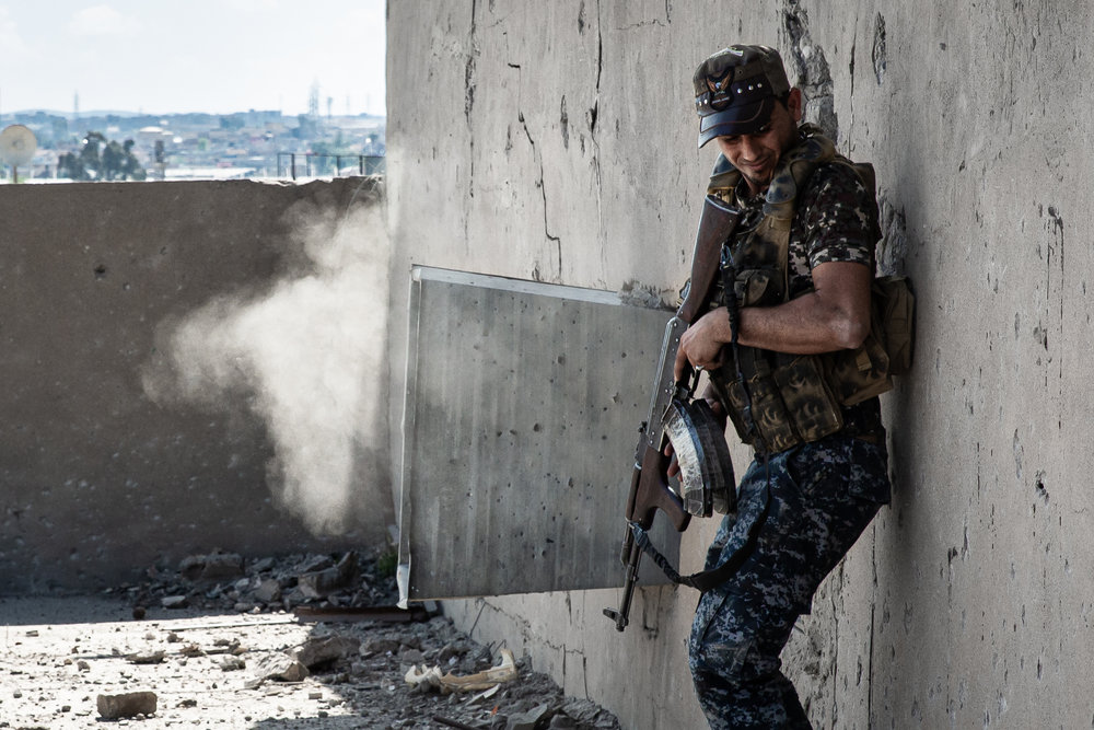 A Federal Policeman reacts as Islamic State bullets impact the other side of the wall near him. Police were fighting Islamic State for control of this cinema in west Mosul.