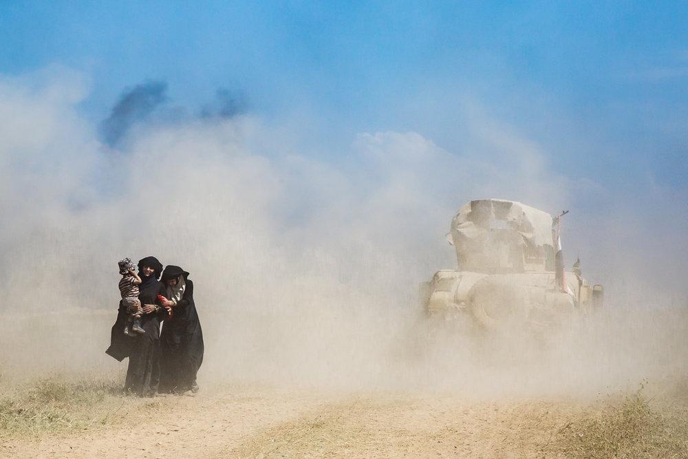 A Humvee passes civilians fleeing battles in Musharrifah, northwest Mosul.