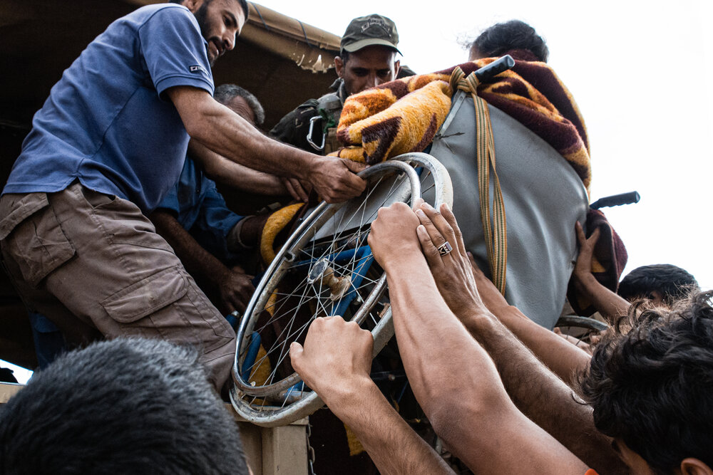 Men help a woman into the back of a covered military transport at Iraqi Army lines in Musharrifah