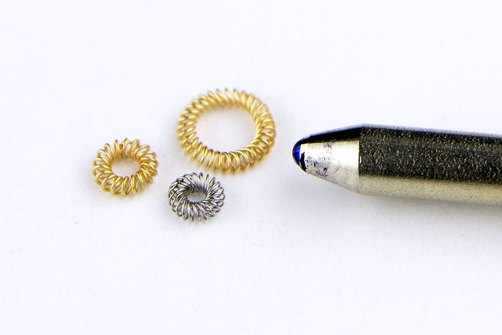 CANTED COIL MICRO DYNAFLEX™ SPRINGS COMPARED TO A PEN TIP