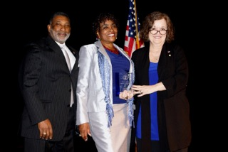 Corinne Anderson (center), recipient of the Evelyn Gandy Award, is congratulated by State Rep. Oscar Denton and State Committee member Pam Johnson