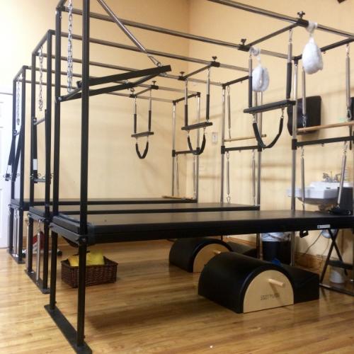 SOMA Movement Studio's group Trapeze Tables in our Equipment Gym. Notice the white, fuzzy hanging straps that can be used to suspend the entire body as well as the spring loaded trapeze bars that hang from the overhead, horizontal poles. Tower units are not able to replicate Cadillac exercises that use the overhead, horizontal poles.