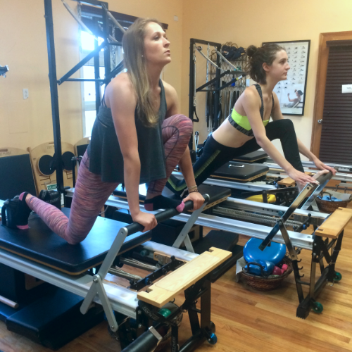 A photo of two women in one of SOMA's Pilates Reformer classes working on hamstring and hip flexibility.