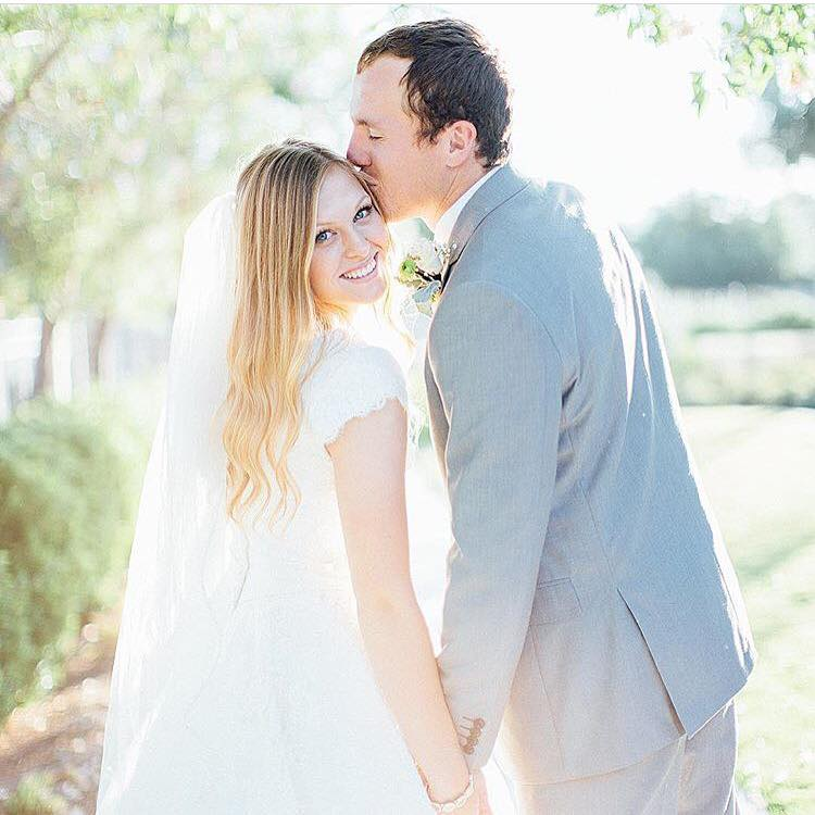 McKenzie is glowing with a kiss in her stunning modest wedding dress