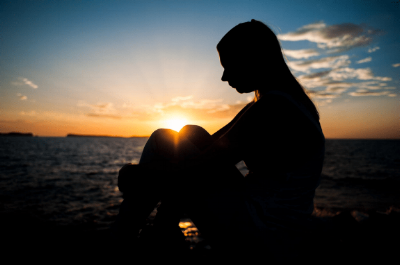Woman's silhouette against sunset on water