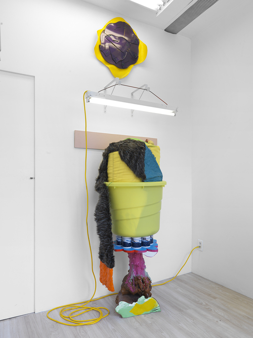 Untitled , 2009 vinyl, fluorescent fixture, electric cord, cable, hardware, yellow plastic tub, yellow laundry bag, Styrofoam stuffing, artifical lemons, acrylic and oil paint, coffee mugs with custom image, wooden base, ribbon, fake fur, plastic parts 109 x 37 x 40 in; 276.9 x 94 x 101.6 cm