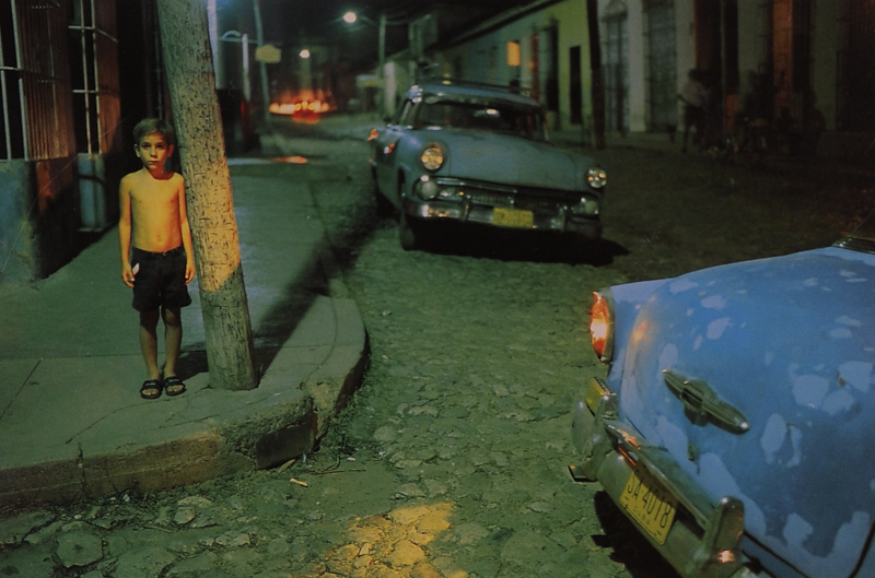 """Photo by David Alan Harvey, published in """"Cuba."""" """"Many of Trinidad's cobblestone streets have a distinct slope to the center. Most say it's for the drainage-- others insist an early Trinidad governor's right leg was shorter than his left, and that he had the streets built on a slant so he could walk without a limp."""""""
