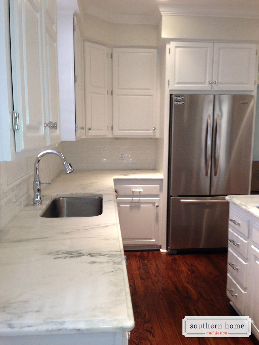 Updated University Park kitchen with white raised panel cabinets, exposed hinges, honed Danby marble countertops, wood floors, stainless steel appliances.