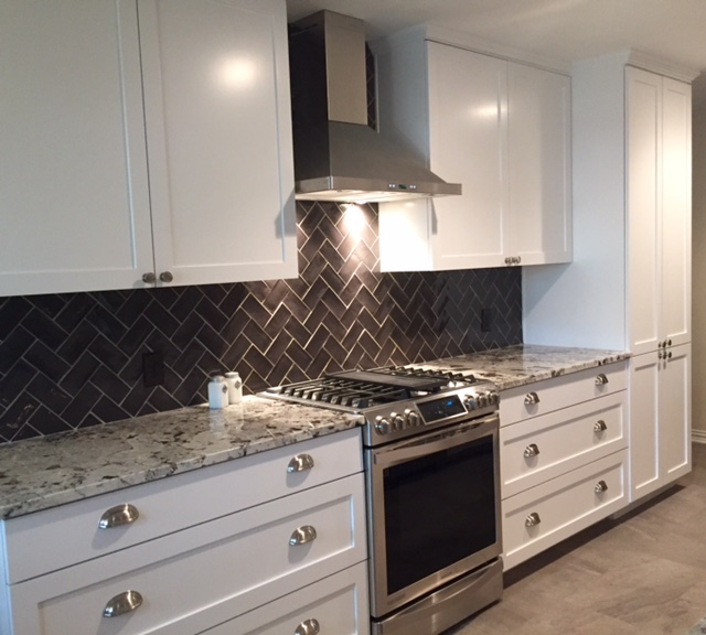 Galley kitchen opened into family room. White shaker style cabinets.