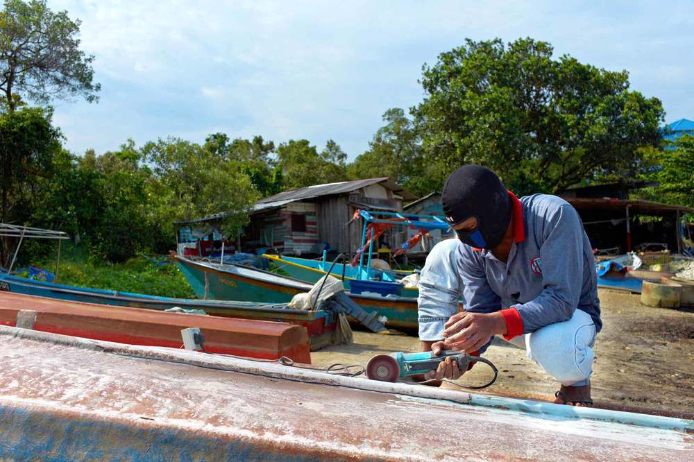Fishermen works on repairing the hull of the boats
