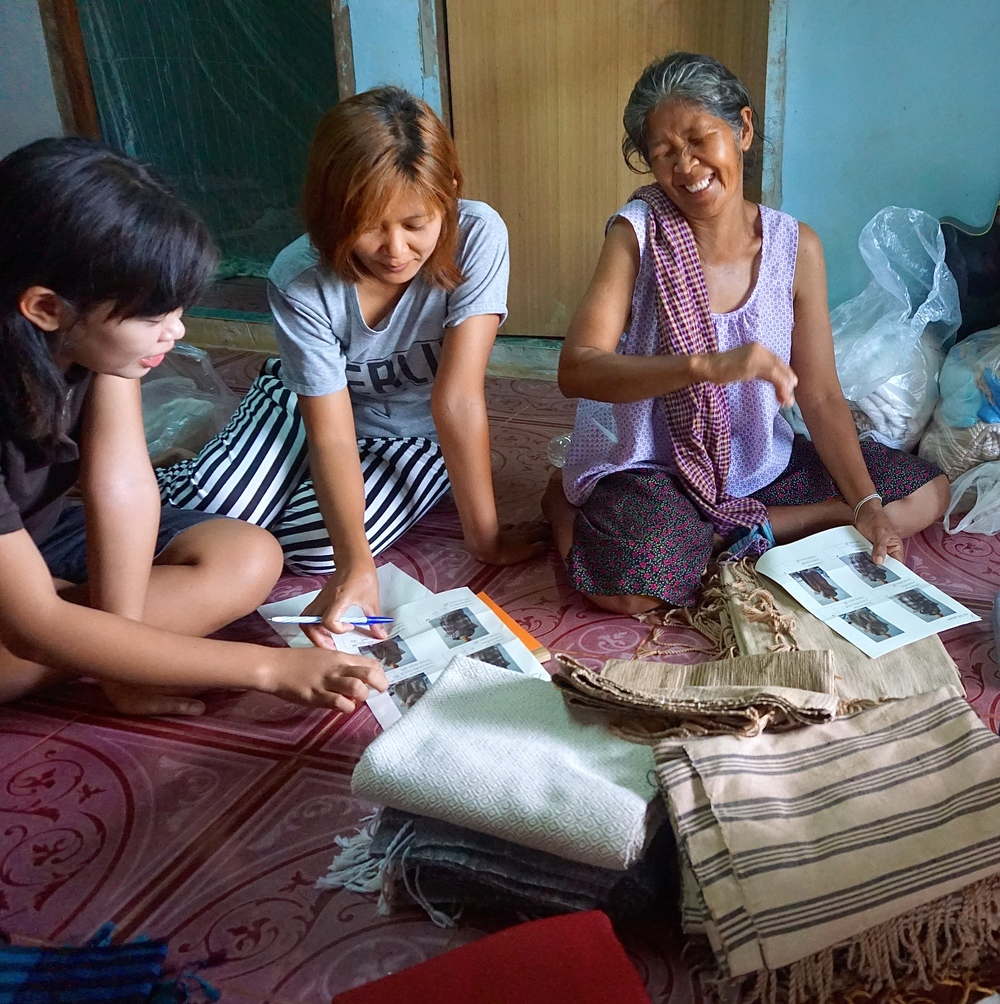 For the Kongsaens, the Radical Grandma Collective requires help from the whole family.  Mae Rote  and her daughters, Rote and Toom, read the order forms together.