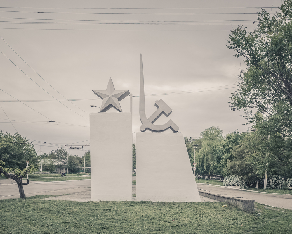 LINKS TO THE MOTHER LAND TRANSNISTRIA | 2015   When communism and Christianity go hand in hand on the roadside.   Transnistria is a narrow strip of land wedged between the Dniester River and the Ukrainian border. Ghost state, Transnistria, 4200 km2 and 500 000 inhabitants, has acquired the attributes of a state: it has its own currency (the Transnistrian ruble), its anthem, a Supreme Soviet, a flag with a hammer and sickle. The region is entirely focused on Russia, which it has served for two centuries.   This tiny territory, trapped between Moldova and Ukraine, has an incredible amount of Soviet monuments that are still perfectly maintained for the most part over 20 years after the fall of the USSR. Here, nothing was destroyed or taken apart. The communist system has since long disappeared giving way to an unbridled market economy to the delight of a few hundred oligarchs ... But these old monuments installed on the roadside and the village squares, are more meaningful than ever to the local population: they belong to that great Russian power from the Soviet era.   A kind of surprising visual syncretism has developed, particular to this region. Thousands of Orthodox crosses have joined the communist monuments over the past 20 years. Religious symbols linked to the rebirth of Christianity in the region. Political symbols as well, of the strong bond with the Moscow patriarchate and of the fact that Transnistria was and should be part of the great imperial Russia.