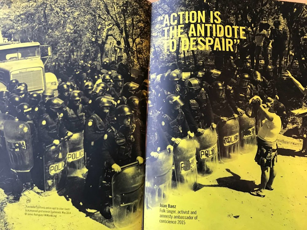 A Joan Baez quote, 'Action is the antidote to despair' to illustrate a protestor standing up to riot police.