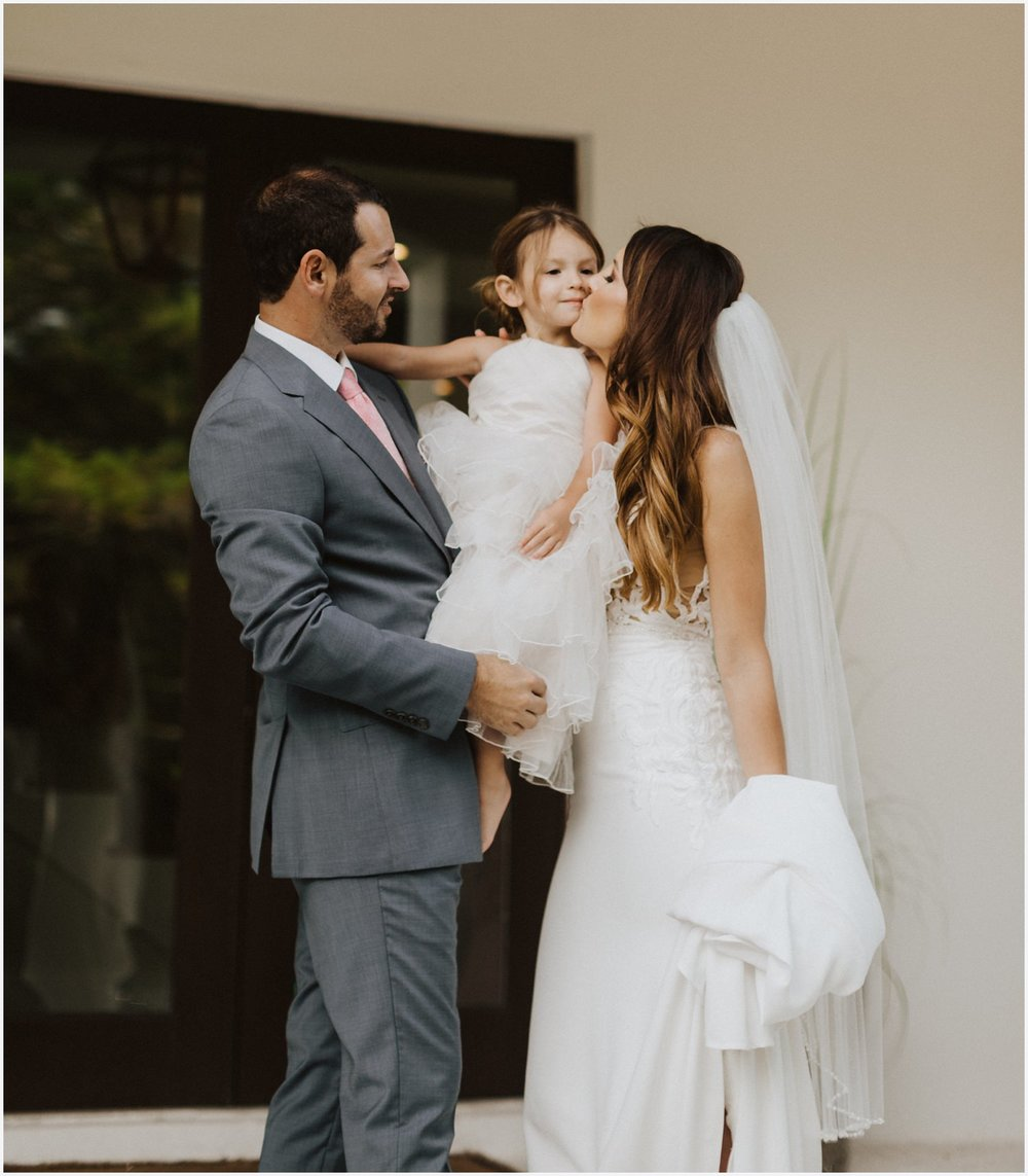 Bride and groom kissing their daughter at their Rosemary Beach house