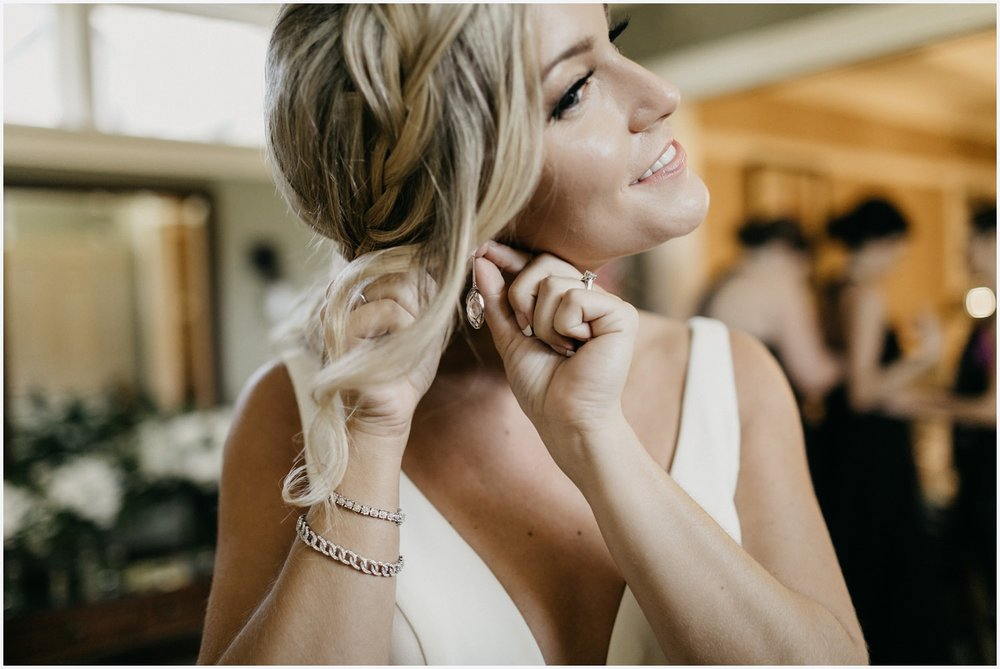 Bride putting her wedding jewelry on at the Shark's Tooth Golf Club