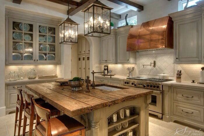 Elegant Wrought Iron Pendants Creating A Focal Point In A French Country Kitchen.