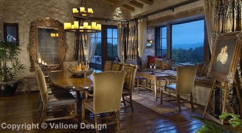 A rustic dining room with a double tier wrought iron Mallorca Chandelier.