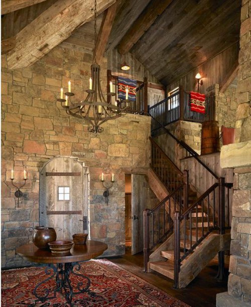 Monaco Chandelier and wrought iron sconces in a rustic stone entryway.