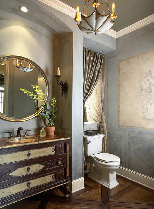 A feminine, Mediterranean style bathroom with Laura Lee Designs sconce.