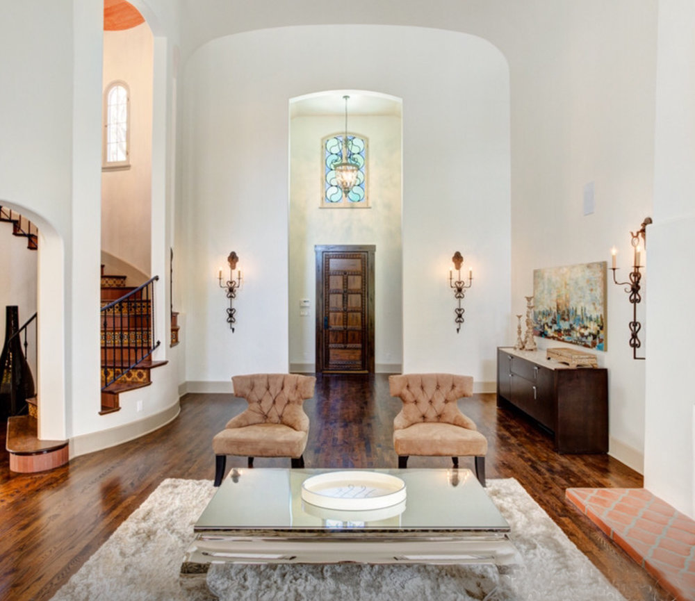 Entryway and living room of a Spanish Revival home with Laura Lee Designs sconces.