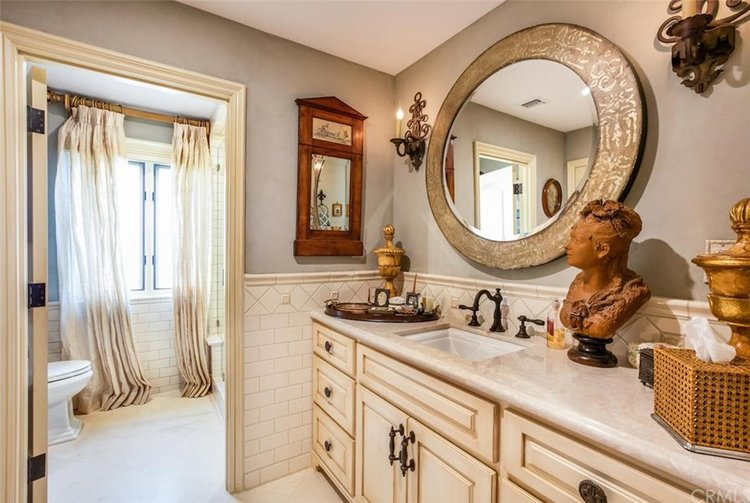 Fleur De Lis sconces gracing a master bathroom.