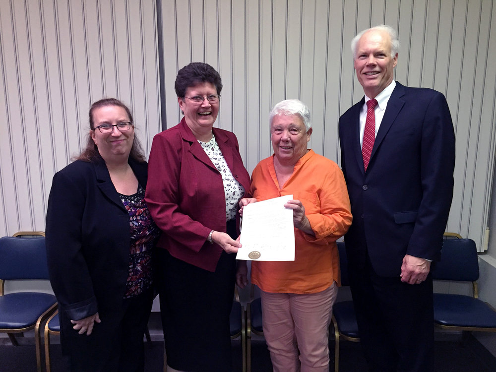 Franciscan Child Day Care Center Director Sandy Merlo and Board President Sister Janet receive a copy of resolution 948 from Mayor Jim Nowalk and Whitehall Borough Council President Kathy N. DePuy.