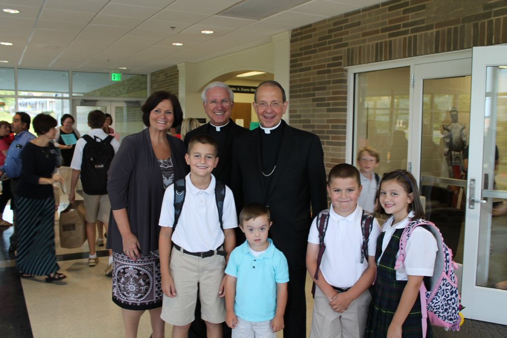 Dr. Barbara Edmondson (Superintendent of Catholic schools for the Archdiocese of Baltimore) Monsignor Joseph Luca (pastor of St. Louis Catholic Church) and Archbishop William Lori (Archdiocese of Baltimore) pose with the Remick children Bergen (11), Tobin (4), Carsten (9) and Zoe (7).