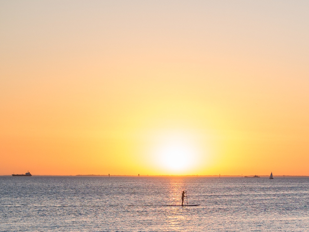 A paddle boarder enjoys the sunset at St Kilda, Melbourne.