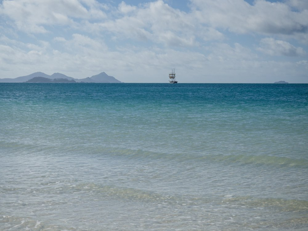 A ship sails away from Whitehaven beach.