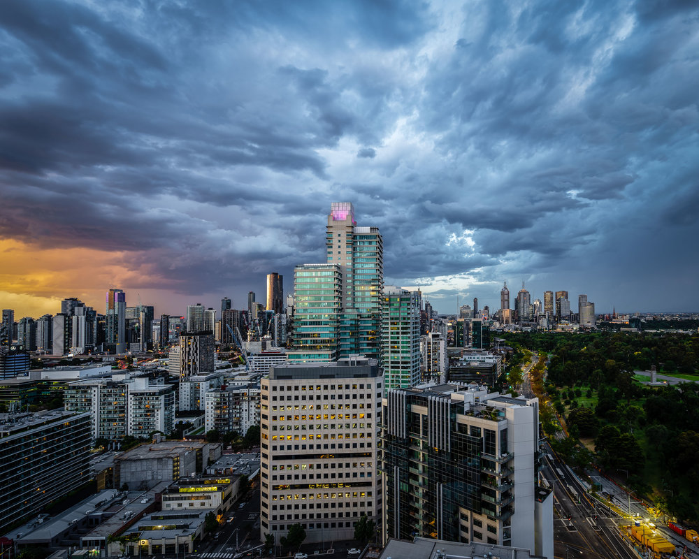 Storm clouds gather over Melbourne as the sun sets.