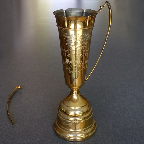 Hawkins Vintage Trophy with yellow discolored lacquer and broken handle.