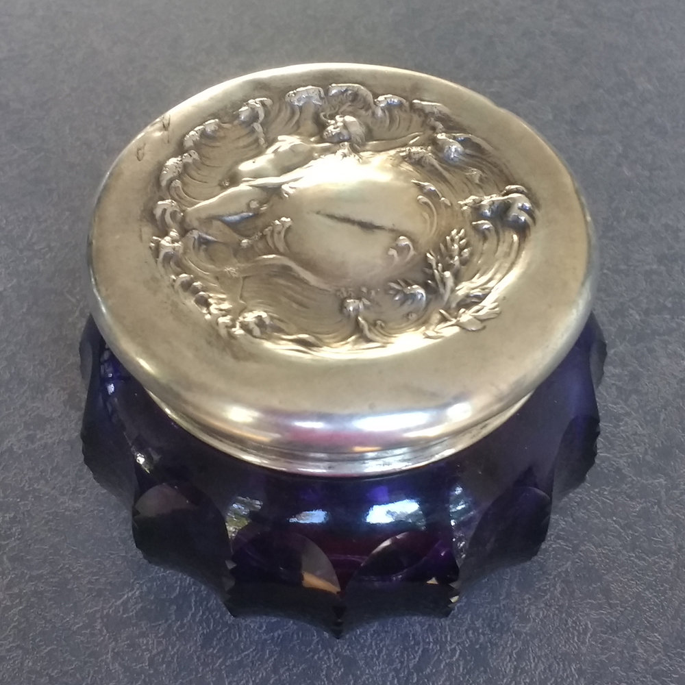 Sterling silver dresser set lid with sharp dent across the top and many small dents.