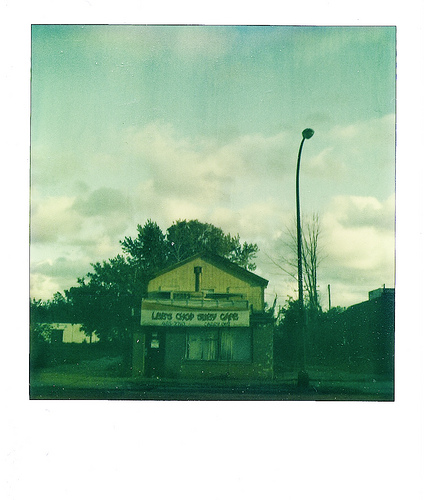 Leo's Chop Suey Cafe  (by  ericarhiannon )   I took this with my SX 70 a few weeks ago when the sun light was creating some awesome shadows on this abandoned restaurant. I had to mess with the scan a bit as the original is slightly flat.  They just tore this place down a few days ago.